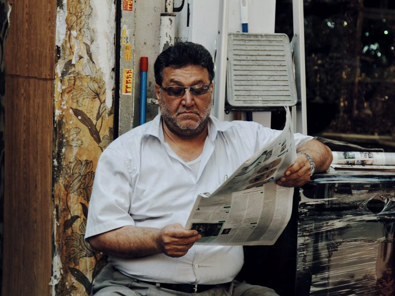 man in white polo shirt reading newspaper
